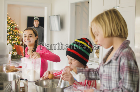 teenage girl and brothers baking in