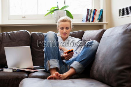 young woman sitting on sofa and