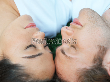 young couple sleeping in field