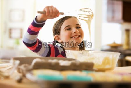 girl mixing cake batter in bowl