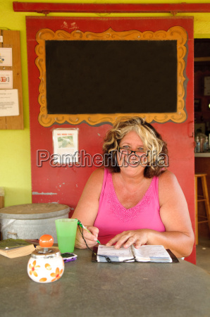 woman writing in notebook at cafe