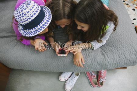 three girls using smartphone high angle