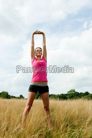young woman stretching in a field