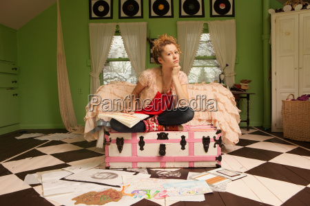 teenage girl sitting on ottoman with