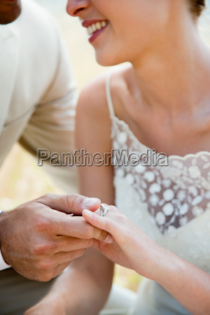 newlyweds looking at wedding ring close