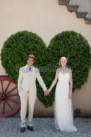 newlyweds by heart shaped bush holding