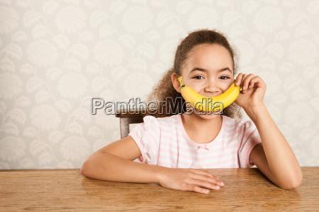 girl holding a banana over her