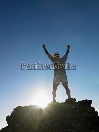 man standing on top of rock
