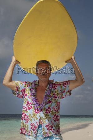 senior man holding surfboard portrait