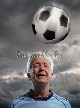 senior man heading football