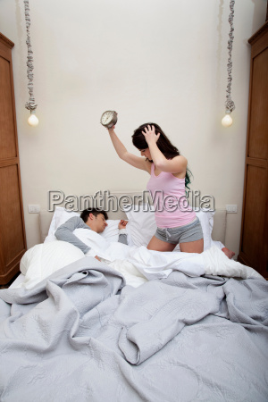couple in bed woman holding alarm