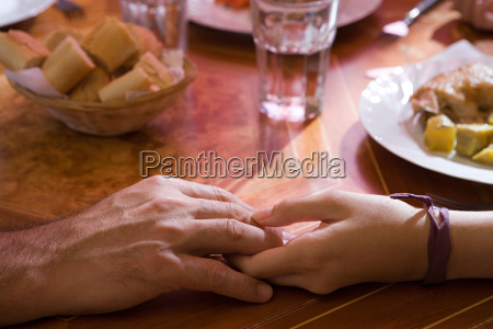 holding hands at the dinner table