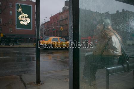 man looking at billboard from bus