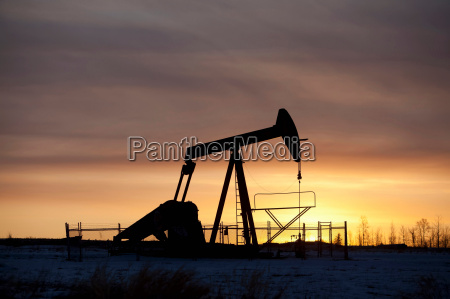 silhouette of oil well at sunset