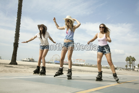three young women inline skating