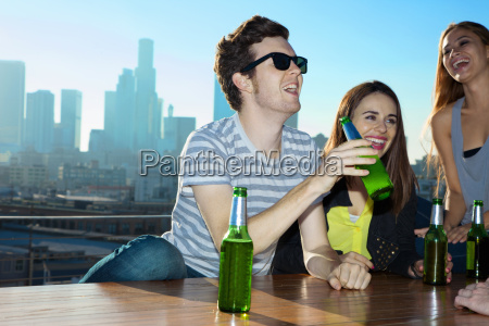 young women and man drinking beer