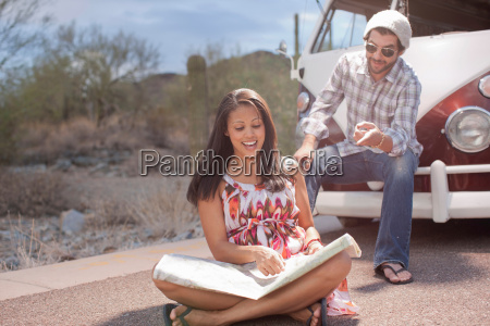 young woman sitting in road reading