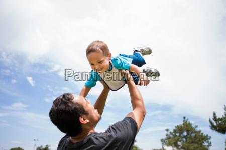 young man playing lifting up toddler