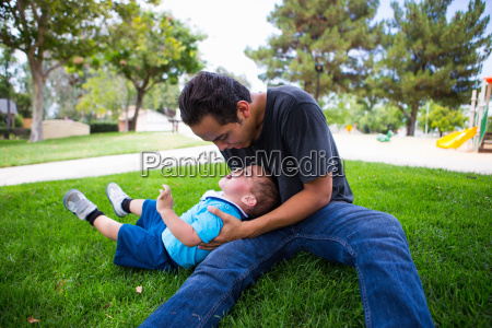 male toddler playing with older adult
