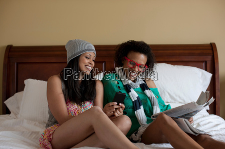 young women sitting on bed using