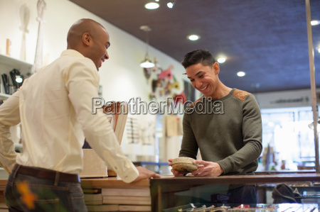young man buying item from shopkeeper