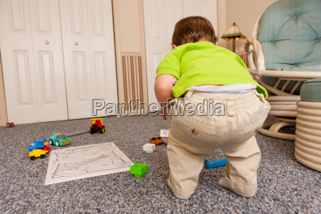 young male toddler playing with toys