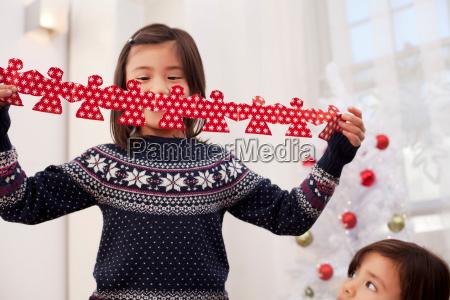 girl holding christmas decorations