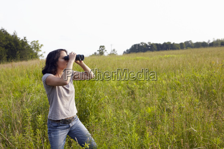 woman looking through binoculars from field