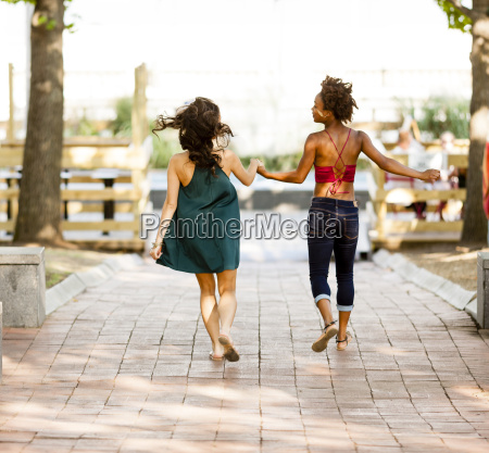 young women walking on cobbled street