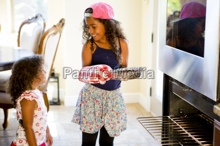 girl watching big sister insert cake