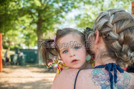 baby girl looking over mothers shoulder