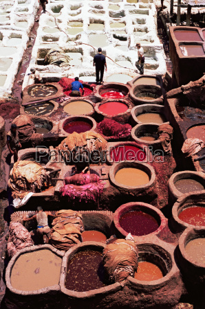 workers at leather dyeing vats in