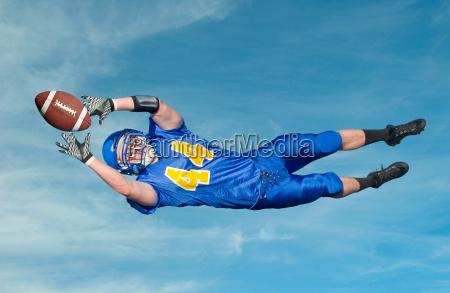 american footballer catching ball against blue