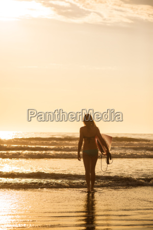 young woman with surfboard at sunset