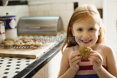 portrait of girl eating biscuit in