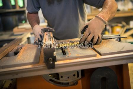 wood artist in workshop using woodworking