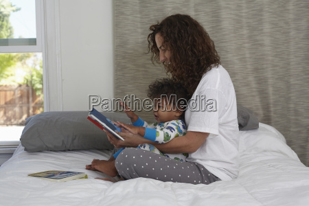 young woman sitting on bed reading
