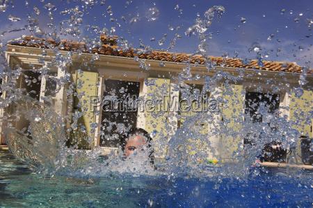 teenage girl splashing in outdoor swimming