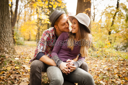 romantic young couple sitting in autumn