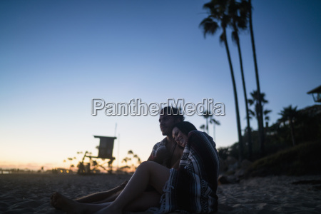 romantic young couple sitting on beach