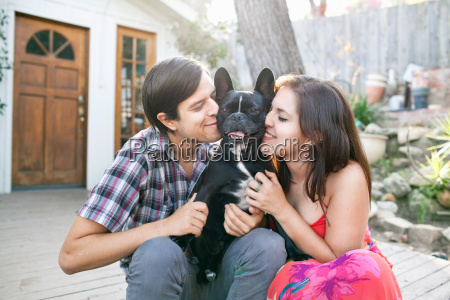 young couple sitting on patio snuggling