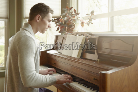 young man playing the piano in