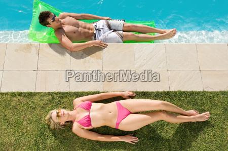 couple sunbathing at the pool