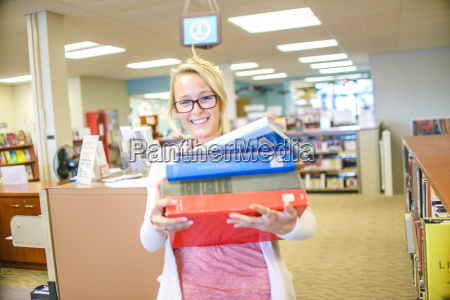 portrait of young female librarian carrying