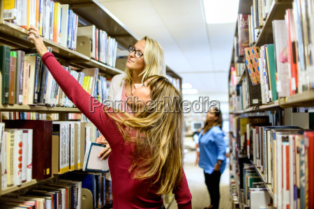 female librarian and customer searching for