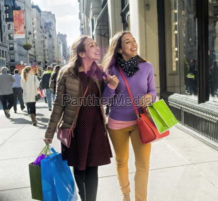 young female adult twins carrying shopping