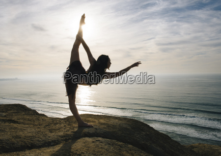 young female dancer standing on rock