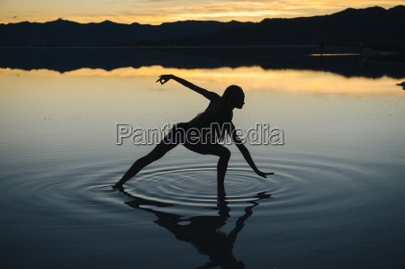 silhouetted female dancer poised in lake