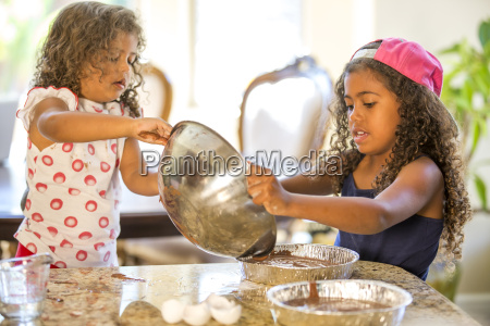 girls pouring cake mix from mixing