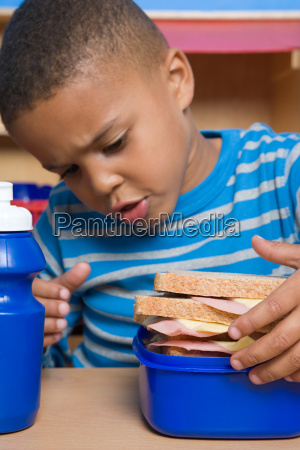boy looking at lunch box